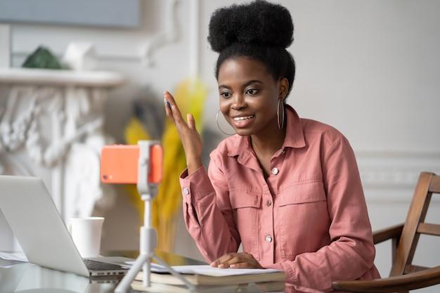 Mulher afro-americana do milênio com controle remoto de penteado afro, estudando, trabalhando online no laptop, conversando com amigos através de videochamada em smartphone no tripé. blogger de gravação de blog de influenciador do blogger.
