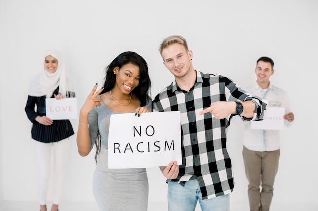 Mulher afro-americana e homem caucasiano segurando cartaz juntos com texto sem racismo