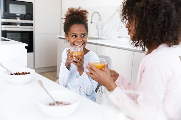 Mulher afro-americana e sua filha bebem suco de laranja enquanto tomam o café da manhã em casa