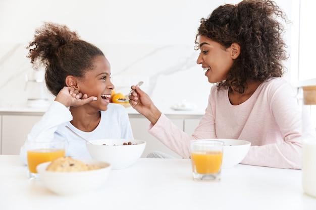 Mulher afro-americana e sua filha tomando café da manhã e comendo flocos de milho na cozinha