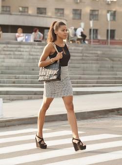 Mulher afro-americana elegante andando na faixa de pedestres ou travessia de pedestres.