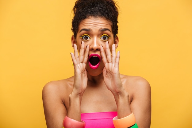 Mulher afro-americana elegante animada brilhante emocionalmente gritando ou chamando a câmera colocando as mãos na boca isolada, sobre parede amarela