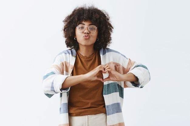 Mulher afro-americana elegante e moderna, sociável, de óculos e casaquinho listrado estiloso, mostrando o sinal do coração sobre o peito, dobrando os lábios em um beijo ou mwah expressando simpatia e afeto