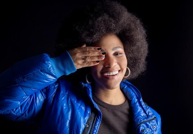 Mulher afro-americana em fundo preto, cobre os olhos com a mão sorrindo