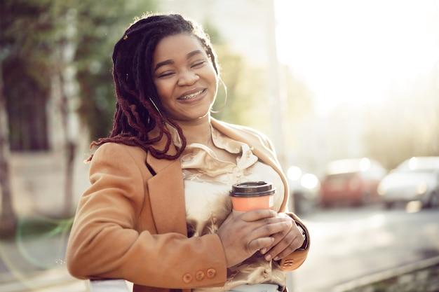Mulher afro-americana em pé em um srteet com uma xícara de café para viagem