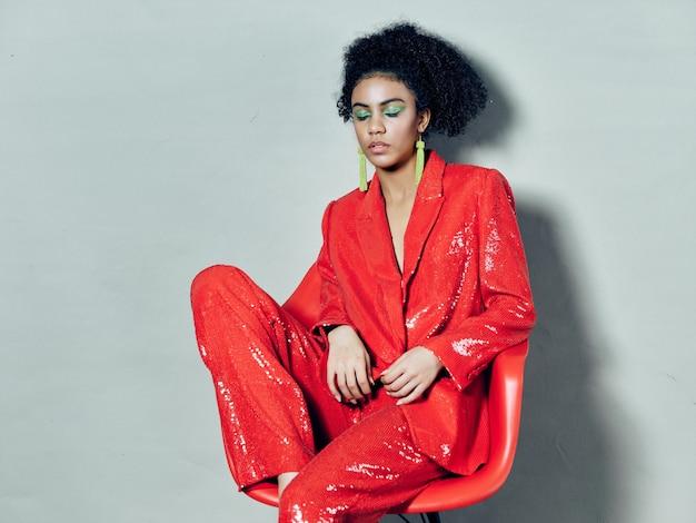 Mulher afro-americana em roupas de moda festiva brilhante em um espaço colorido posando