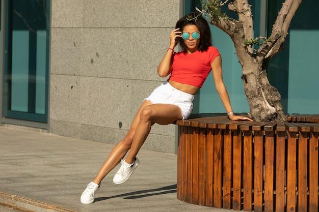 Mulher afro-americana em shorts jeans branco andando pela rua.