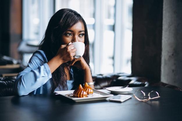 Mulher afro-americana em um café, comer a sobremesa