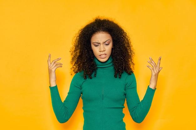 Mulher afro-americana em um espaço de camiseta em um espaço colorido posando