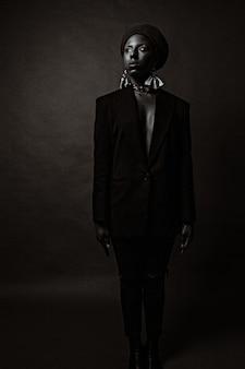 Mulher afro-americana em um terno preto com brincos grandes, posando em um estúdio