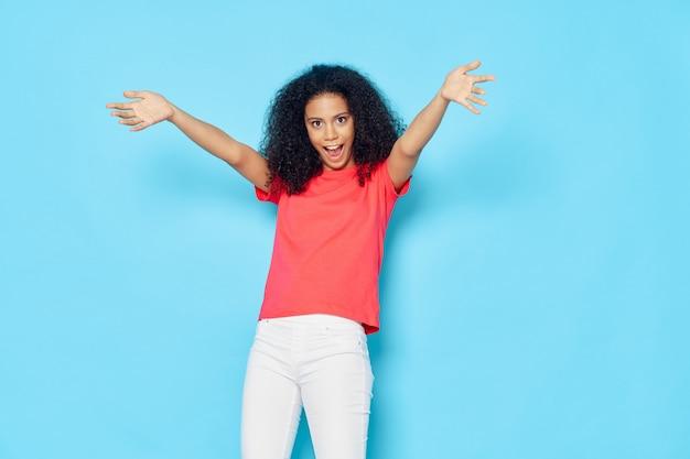 Mulher afro-americana em uma camiseta no estúdio em azul