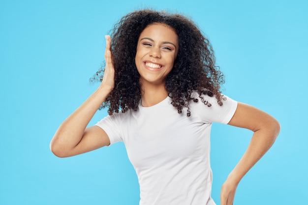 Mulher afro-americana em uma camiseta no estúdio em uma superfície colorida posando