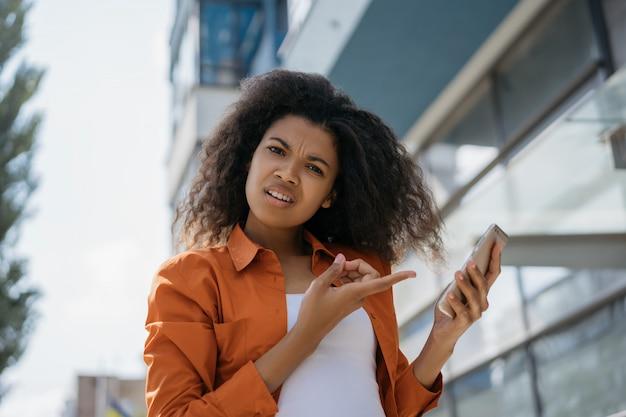 Mulher afro-americana emocional, apontando o dedo na tela do celular