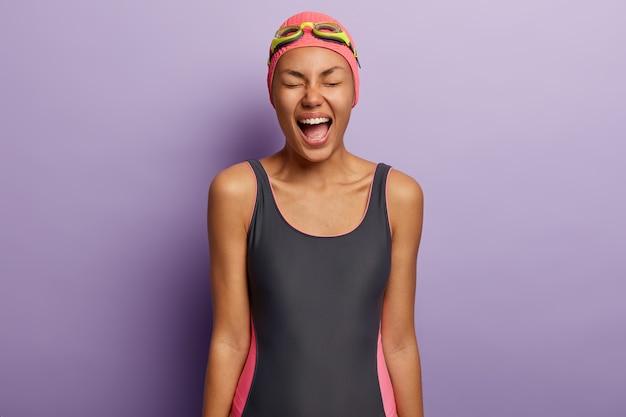 Mulher afro-americana emocional grita bem alto, mantém a boca bem aberta