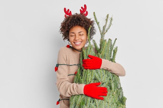 Mulher afro-americana encantada com um sorriso e chifres de rena e luvas, abraça um pinheiro verde com amor, feliz por celebrar o ano novo em casa, retorna do mercado de rua de natal embrulhado em guirlanda