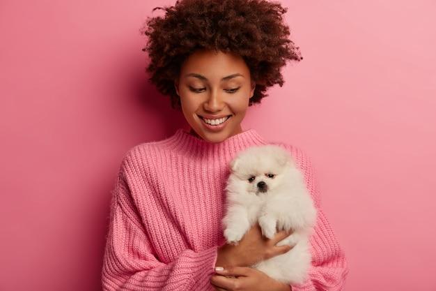 Mulher afro-americana encantada olha com alegria para seu novo animal de estimação, segura um cachorro spitz branco, usa um macacão grande, sorri amplamente, isolado sobre um fundo rosa.