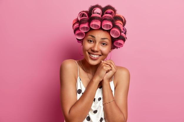 Mulher afro-americana encantadora adulta de pele escura positiva aplica rolos de cabelo, tem um sorriso terno, vestida com roupas casuais, poses
