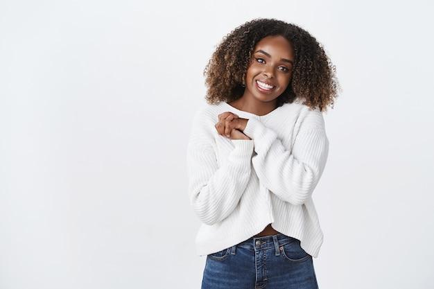 Mulher afro-americana encantadora e feliz, sorridente, de cabelo encaracolado, vestindo um suéter branco, pressione as palmas das mãos juntas gesto de agradecimento, agradecido, olhando a câmera