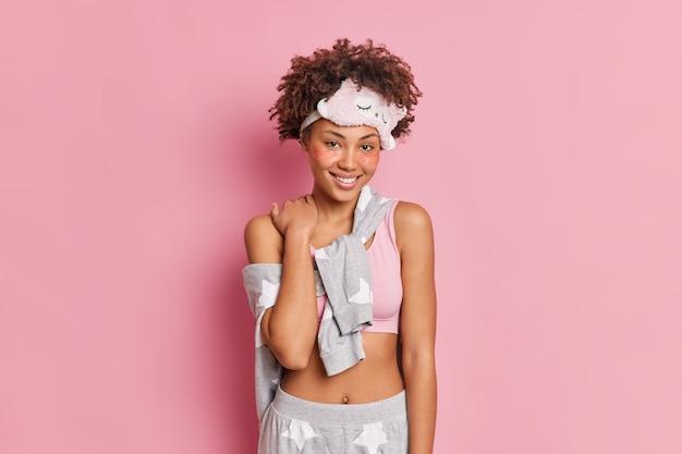 Mulher afro-americana encantadora e satisfeita sorri suavemente, usa macacão e passa por procedimentos de beleza depois de acordar se levanta de bom humor isolada sobre parede rosa
