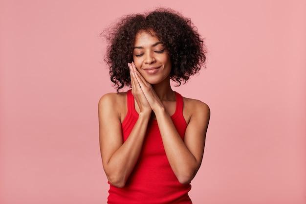 Mulher afro-americana encantadora satisfeita com penteado afro sente prazer, toca o rosto com a palma da mão, olhos fechados, se regozija, mãos postas como sonolentas, vestindo camiseta vermelha, isolado