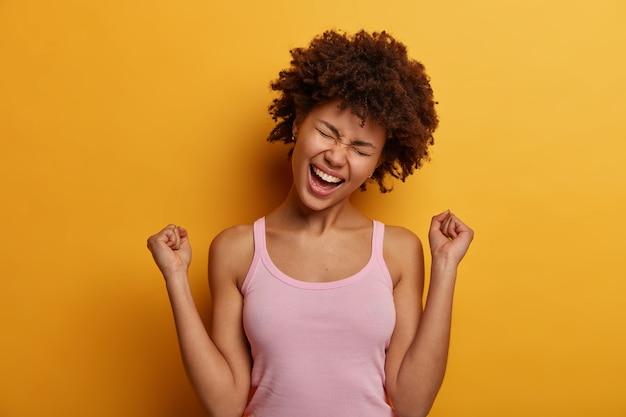 Mulher afro-americana encaracolada e animada fecha os punhos em triunfo, comemora boas notícias, inclina a cabeça e exclama de alegria, sendo a sortuda vencedora, vestida com roupa casual, isolada sobre a parede amarela