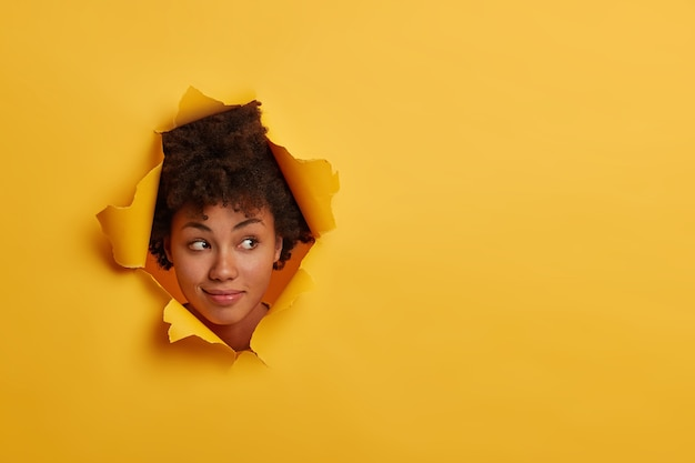 Mulher afro-americana encaracolada olha com expressão curiosa à parte, nota algo interessante, tem beleza natural, isolada sobre fundo amarelo