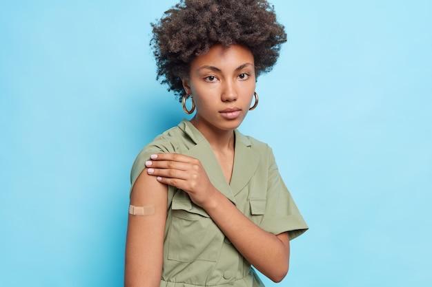 Mulher afro-americana encaracolada séria mostra braço engessado que recebeu segunda dose de vacina e usa vestido parece diretamente na frente isolado sobre a parede azul