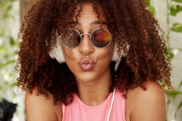 Mulher afro-americana engraçada com lábios arredondados, faz careta, tem pele morena saudável, cabelo crespo e espesso, usa óculos escuros, ouve faixa de áudio em modernos fones de ouvido brancos. conceito de juventude e lazer.
