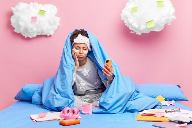 Mulher afro-americana entediada e descontente enrolada em um cobertor fazendo videochamada vestida de pijama