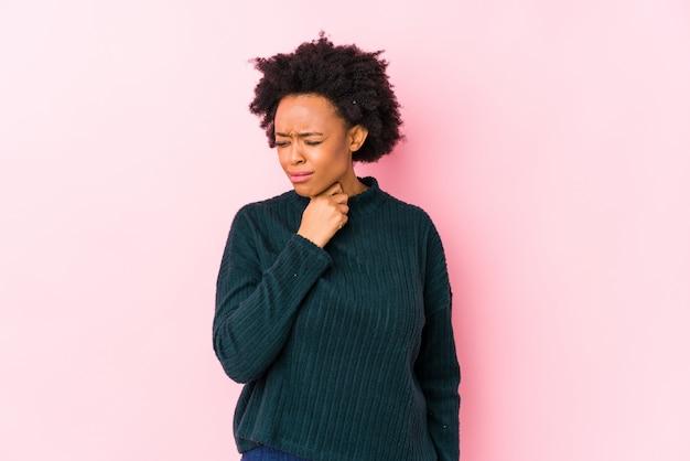 Mulher afro-americana envelhecida média contra rosa