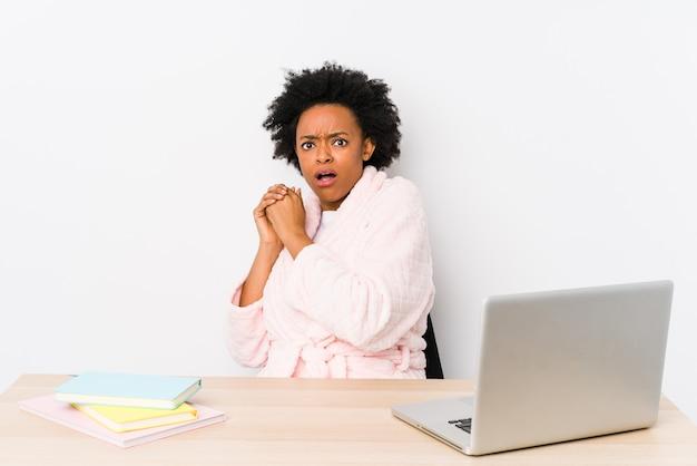 Mulher afro-americana envelhecida média que trabalha em casa assustado e com medo.