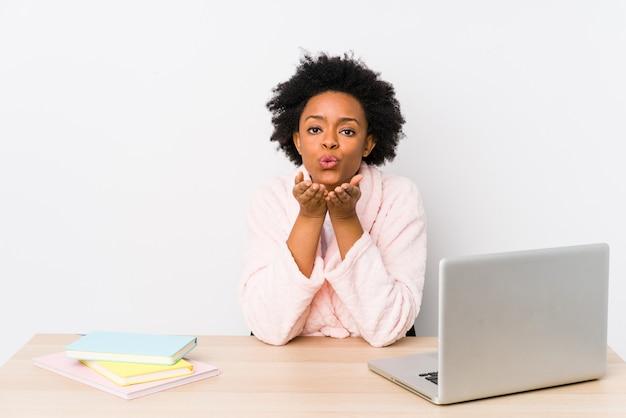 Mulher afro-americana envelhecida média, trabalhando em casa, dobrando os lábios e segurando as palmas das mãos para enviar beijo de ar.