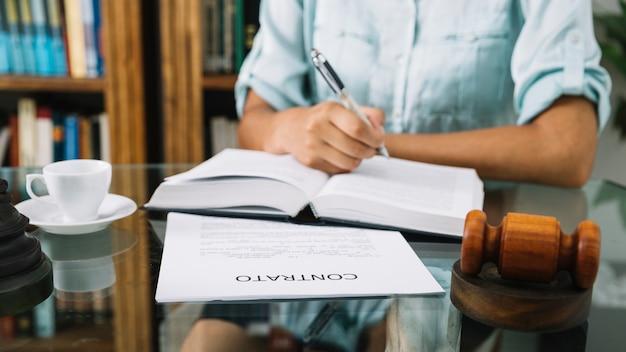 Mulher afro-americana, escrevendo no livro na mesa com copa e documento