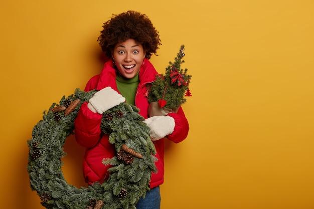 Mulher afro-americana espantada e surpresa segurando uma coroa de flores verdes e uma árvore de abeto, tem uma expressão alegre, se prepara para o natal ou ano novo, isolada sobre a parede amarela.