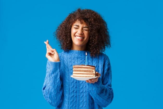 Mulher afro-americana esperançosa e animada, bonita camisola, fazendo desejo e cruzar os dedos