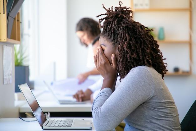 Mulher afro-americana exausta, esfregando o rosto