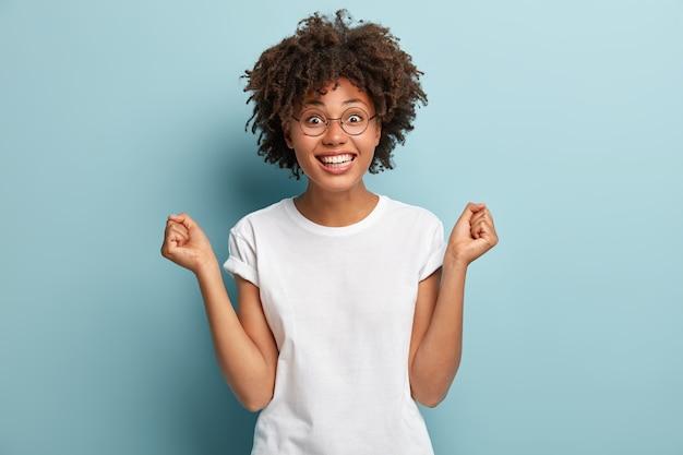 Mulher afro-americana exultante antecipa a vitória, fecha os punhos, tem um sorriso largo