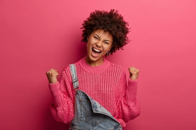 Mulher afro-americana exultante e jubilosa celebra a vitória, alcança o sucesso, exclama com triunfo, veste um suéter, inclina a cabeça, posa sobre uma parede rosa. sendo feliz vencedor. sim, consegui!