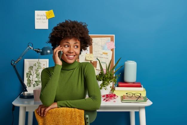 Mulher afro-americana fala pelo smartphone, trabalha na mesa do escritório em casa, tem expressão facial alegre