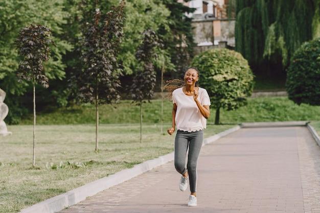 Mulher afro-americana fazendo exercícios no parque em roupas esportivas