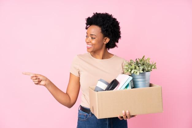 Mulher afro-americana, fazendo um movimento ao longo da parede rosa