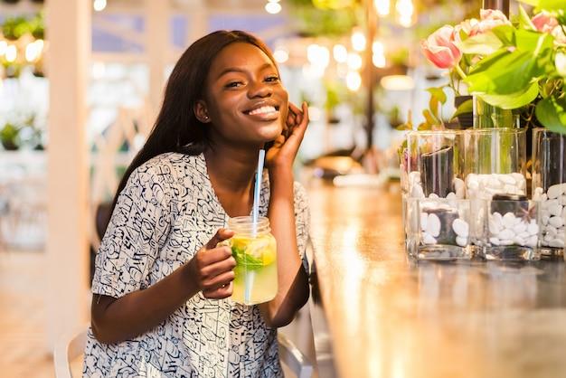 Mulher afro-americana feliz com copo de limonada natural no café. bebida desintoxicante