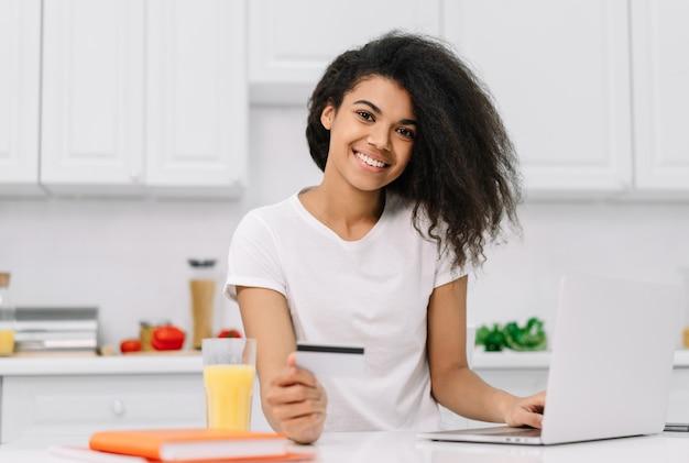 Mulher afro-americana feliz compras on-line, pedir comida, em pé na cozinha. retrato de menina bonita hipster usando laptop, segurando o cartão de crédito, fazer o pagamento, trabalhando em casa