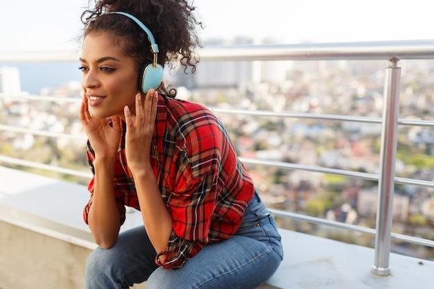 Mulher afro-americana feliz desfrutando de uma música adorável por fones de ouvido, vestida com camisa quadriculada, de pé no telhado. fundo de paisagem urbana.