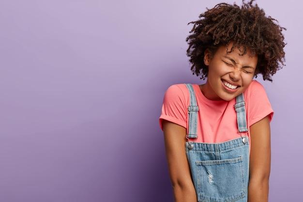 Mulher afro-americana feliz e cheia de alegria começa a rir, fecha os olhos, tem um sorriso largo, inclina a cabeça, ouve uma piada engraçada