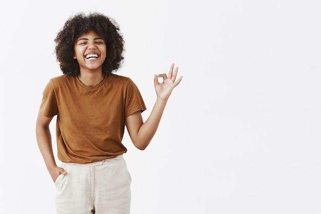 Mulher afro-americana feliz e despreocupada com penteado encaracolado desfrutando de uma ótima companhia, rindo alto e se divertindo, mostrando um sinal de ok ou perfeito com os dedos circulados