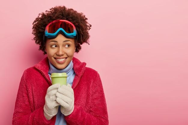 Mulher afro-americana feliz em um casaco vermelho aconchegante, usa máscara de esqui, luvas brancas quentes, bebe café quente, olha para o lado, tem descanso ativo, isolado na parede rosa