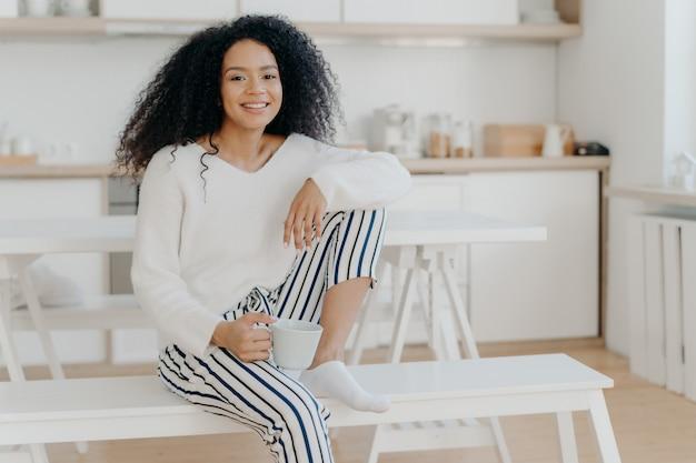 Mulher afro-americana feliz mantém o copo de bebida quente inclina-se no joelho usa branco elegante jumper e calças listradas