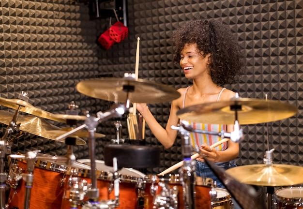 Mulher afro-americana feliz tocando bateria e pratos em um estúdio