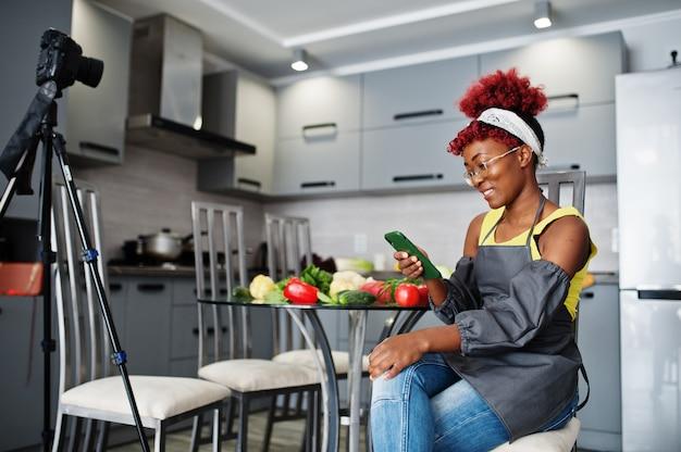 Mulher afro-americana, filmando sua transmissão de blog sobre comida saudável na cozinha de casa e olhando para o telefone.